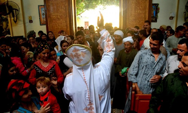 A Coptic Christian priest blesses his congregation with holy water during Sunday service in the Virgin Mary Church at Samalout Diocese in Al-Our village, in Minya governorate, south of Cairo, May 3, 2015. - REUTERS/Stringer