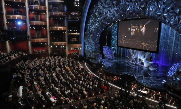 90th Academy Awards - Oscars Show - Hollywood, California, U.S., 04/03/2018 - Host Jimmy Kimmel and actors are shown on the big screen as they deliver candy to people in a movie theatre next door to the Dolby Theatre. REUTERS/Lucas Jackson.