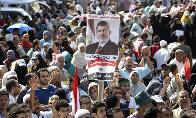 Supporters of MB President Mohamed Morsi, hold his posters as they rally at the Rabaa Adawia square where they are camping - REUTERS