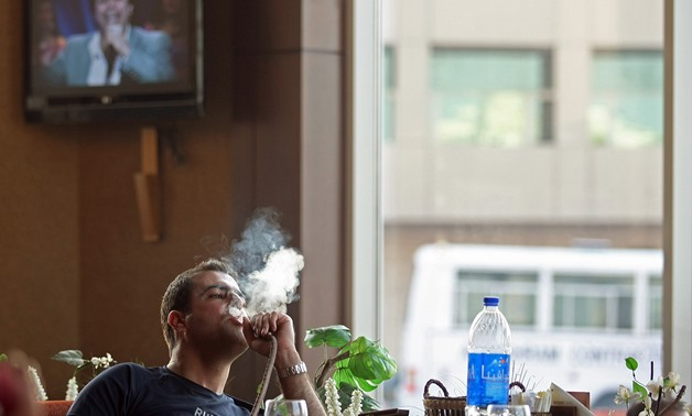 FILE: A young man smoking Shisha in a cafe