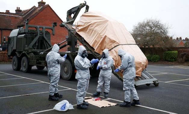 Soldiers wearing protective clothing remove a police vehicle from a car park in Salisbury, Britain, March 11, 2018 - REUTERS/Henry Nicholls. ""