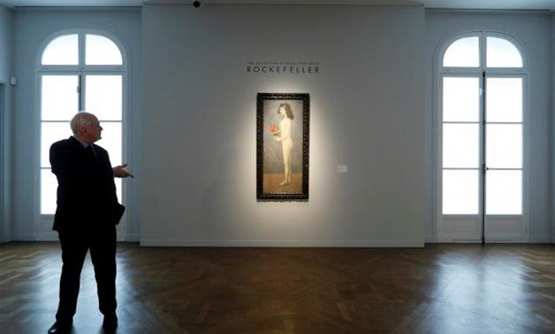 Jonathan Rendell, deputy chairman and senior advisor Christie's Americas stands next to 'Fillette a la corbeille fleurie' by Pablo Picasso from the collection of Peggy and David Rockefeller during a sale preview at Christie's auction house in Paris, Franc