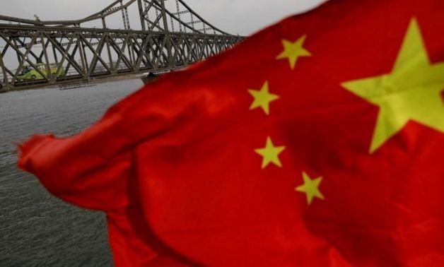 A Chinese flag is seen in front of the Friendship bridge over the Yalu River connecting the North Korean town of Sinuiju and Dandong in China's Liaoning Province on April 1, 2017 - REUTERS/Damir Sagolj/File Photo
