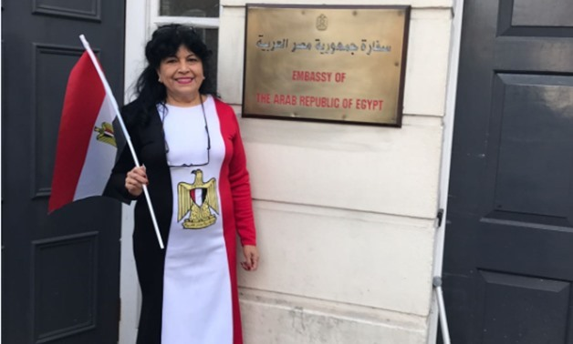 A woman voter wearing a dress of the three Egyptian flag colors outside the Egyptian embassy in London to cast her vote in Presidential election - Egypt Today