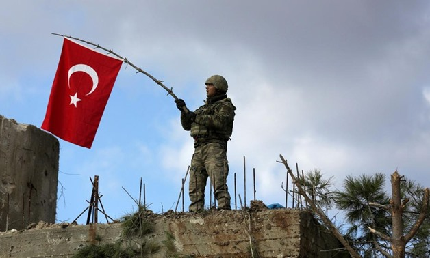 A Turkish soldier waves a flag on Mount Barsaya, northeast of Afrin - REUTERS