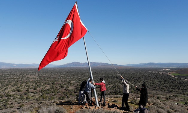 Villagers fix a broken flagpole in Sugedigi village on the Turkish-Syrian border in Hatay province, Turkey, January 2018. REUTERS