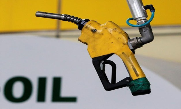 A gas pump is seen hanging from the ceiling at a petrol station in Seoul June 27, 2011. REUTERS/Jo Yong-Hak/File Photo
