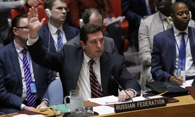 Russian Deputy Permanent Representative to the United Nations Vladimir Safronkov holds up his hand as he votes against a draft resolution that condemned the reported use of chemical weapons in Syria during a meeting at the UN Headquarters in New York, Apr