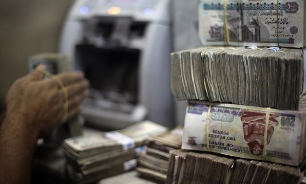 An employee counts money at an exchange office in downtown Cairo (Photo credit: Reuters/Amr Abdallah Dalsh)