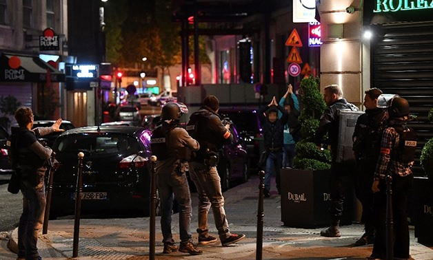 Police check passersby near the Champs Elysees in Paris after a shooting - AFP