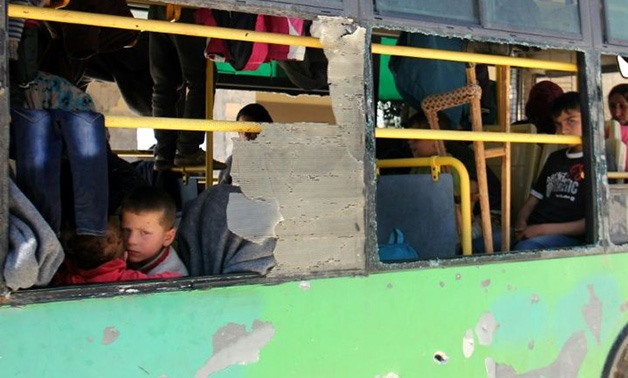 Syrian evacuees from the government-held towns of Fuaa and Kafraya sit in a bus April 20, 2017 - AFP