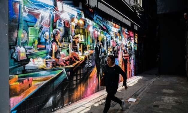 A pedestrian runs past a mural spray painted by British artist Dan Kitchener in an alleyway near a market in the Wanchai district of Hong Kong