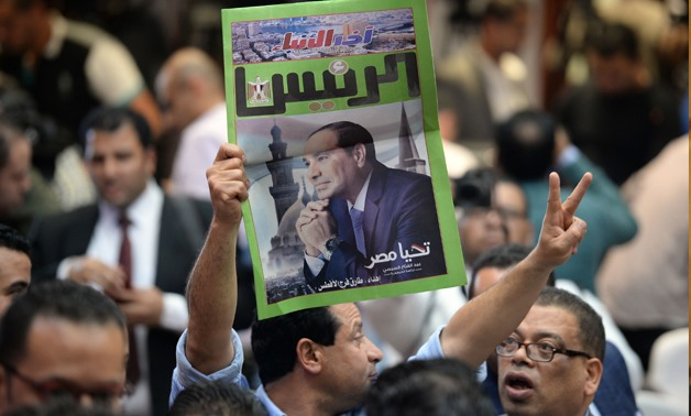An Egyptian man carries a copy of a newspaper, bearing the portrait of Egyptian President Abdel Fattah al-Sisi, during a press conference by the National Elections Authority in Cairo on April 2, 2018, to announce official result of Egypt presidential ele