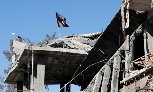 A flag of Islamic State militants is pictured above a destroyed house near the Clock Square in Raqqa, Syria October 18, 2017. REUTERS/Erik D