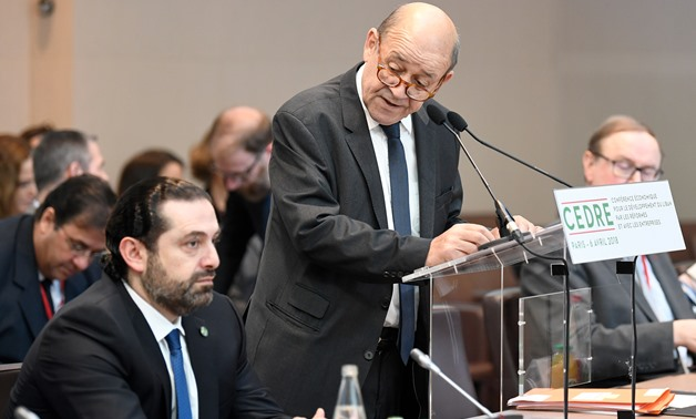 French Foreign Minister Jean-Yves Le Drian delivers his opening speech as Lebanese Prime Minister Saad Hariri (L) listens to during the Cedar (CEDRE) Conference for international donors and investors to support Lebanon's economy, in Paris, France, April 6