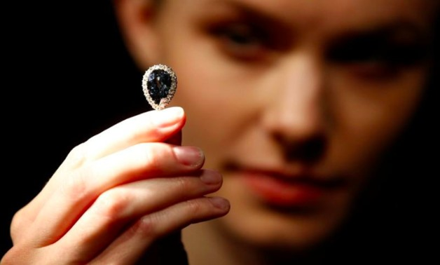 A model poses with 'The Farnese Blue' diamond at Sotheby's auction house in London, Britain, April 6, 2018. REUTERS/Henry Nicholls