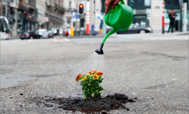 Brussels resident Anton Schuurmans waters flowers after planting them in an unrepaired pothole to draw attention to the bad state of public roads in Brussels, Belgium April 5, 2018. REUTERS/Francois Lenoir