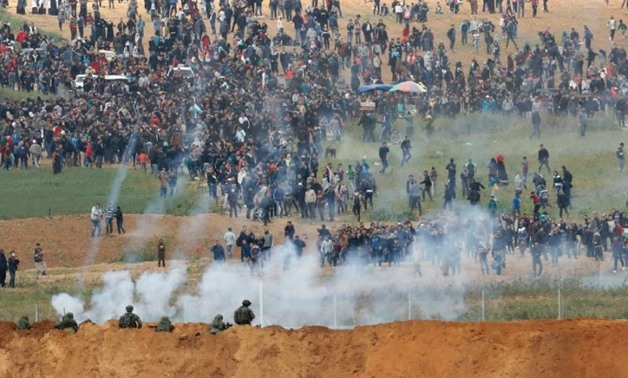 Israeli soldiers fire tear gas as thousands of Gazans march just across the border fence (AFP Photo/Jack GUEZ )