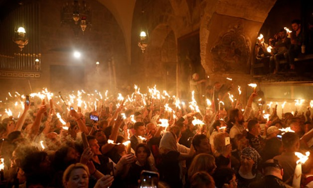 Christians celebrate Holy Saturday by holding up candles lit from the 'Holy Fire' in the Church of the Holy Sepulchre in Jerusalem's old city - file.jpg