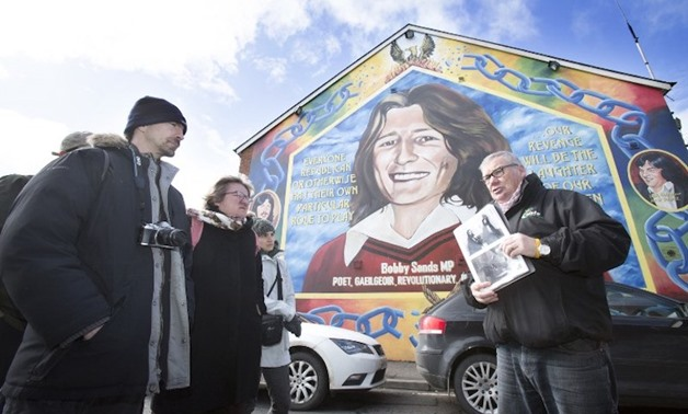 Coiste guide Peadar Whelan (right) talks to his group of tourists in front of a mural to of IRA hunger striker Bobby Sands during a political guided tour in west Belfast March 27, 2018. — AFP pic