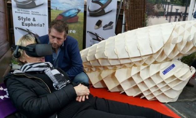 """Dutch designer Alexander Bannink explains how the """"Sarco"""" euthanasia pod works as a woman experiences sitting in the device by wearing virtual reality glasses, on April 14, 2018 at the Amsterdam Funeral Expo - AFP"""