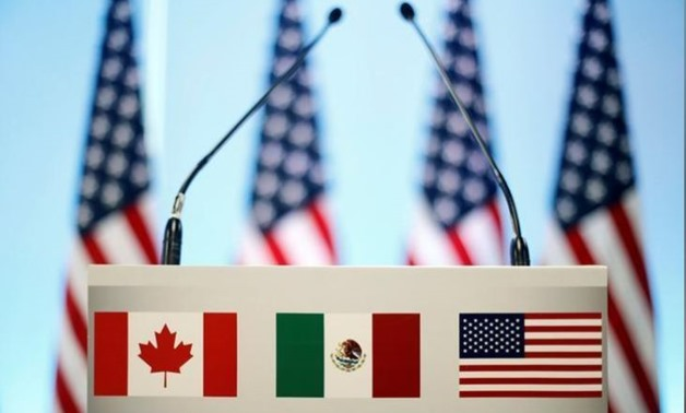 The flags of Canada, Mexico and the U.S. are seen on a lectern before a joint news conference on the closing of the seventh round of NAFTA talks in Mexico City, Mexico March 5, 2018. REUTERS/Edgard Garrido