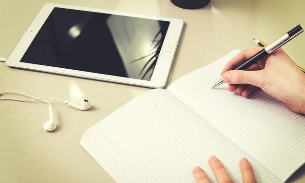 Someone holds a pen with a notebook and a tablet on the table – pixabay/photoMIX-company