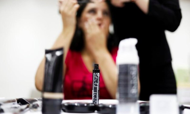 A bottle of Black Mascara writing on it is seen as Maria, 44, who is blind, gets make up put on during a cosmetics class set to help boost self esteem at the Lamara association in Sao Paolo, Brazil, April 18, 2018. REUTERS/Nacho Doce