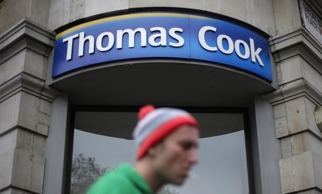 A pedestrian walks past a Thomas Cook shop in central London, November 26, 2014. REUTERS/Suzanne Plunkett