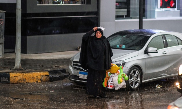 A woman covers herself from the rain in al-Batal Ahmed Abdel-Aziz street, Mohandeseen, Giza - EgyptToday