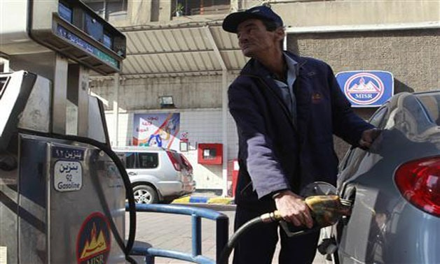 A worker pumps fuel at a petrol station in Cairo January 16, 2011 - REUTERS
