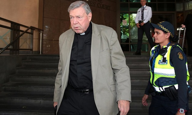 Vatican treasurer Cardinal George Pell is watched by a security guard and an Australian police officer as he leaves Melbourne Magistrates' Court in Australia, March 19, 2018. AAP/Stefan Postles/via REUTERS