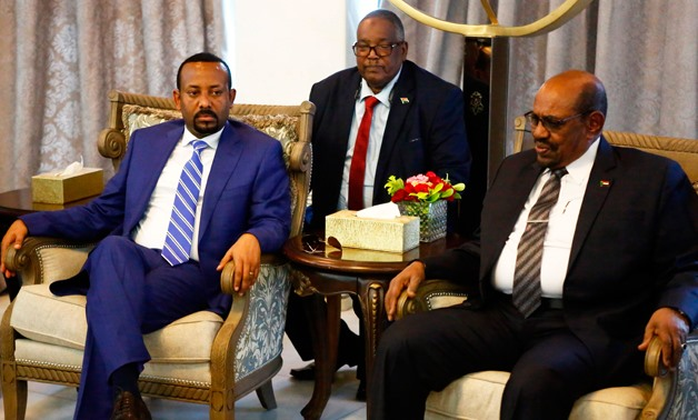 Ethiopian Prime Minister Abiy Ahmed (L) meets with Sudanese President Omar al-Bashir (R) following his arrival in Khartoum for an official visit to Sudan on May 2, 2018. / AFP / ASHRAF SHAZLY
