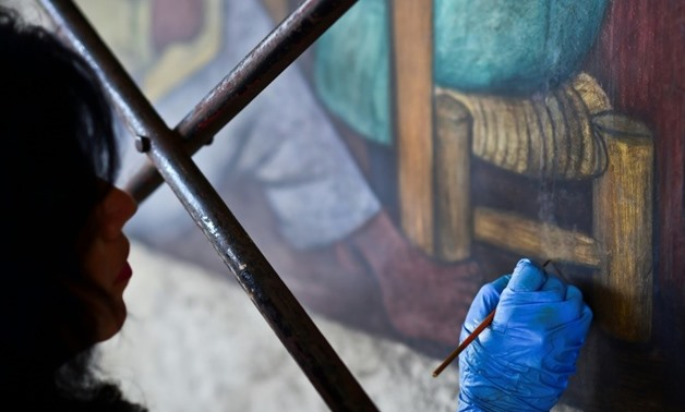 An expert restores a mural by Diego Rivera, whose painting 'The Rivals' now holds the record for the highest price paid at auction for a Latin American artwork-AFP/File / RONALDO SCHEMIDT