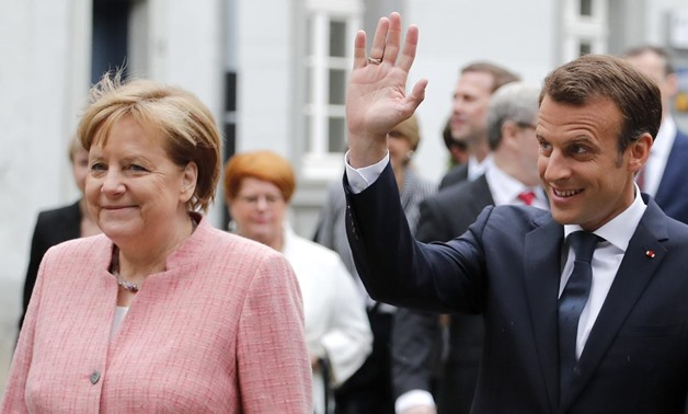French President Emmanuel Macron waves next to German Chancellor Angela Merkel as he arrives to receive a Charlemagne Prize in Aachen, Germany May 10, 2018.