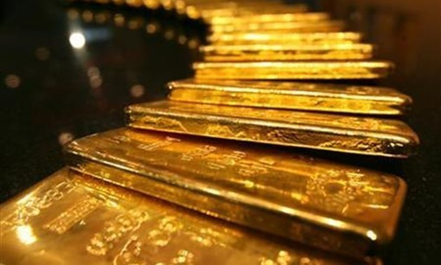 Several one-kilo gold bars are displayed inside a secured vault in Dubai April 20, 2006 - Reuters