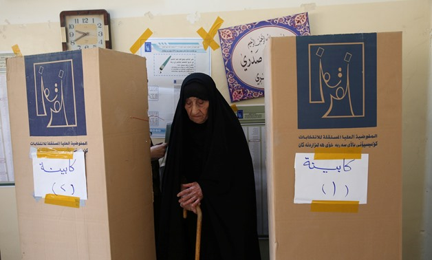 An Iraqi woman prepares herself to cast her vote at a polling station during the parliamentary election in Baghdad, Iraq May 12, 2018. (Reuters)