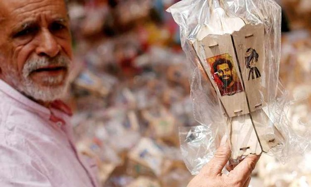 "A man buys traditional decorative lanterns known as ""Fanous"" bearing the image of Liverpool's Egyptian forward soccer player Mohamed Salah at a market, before the beginning of the holy fasting month of Ramadan in Cairo, Egypt May 2, 2018. Arabic words rea"