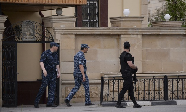 Law enforcement officers walk outside an Orthodox church after the attack of militants in Grozny, Russia May 19, 2018. Picture taken May 19, 2018. REUTERS/Said Tsarnayev