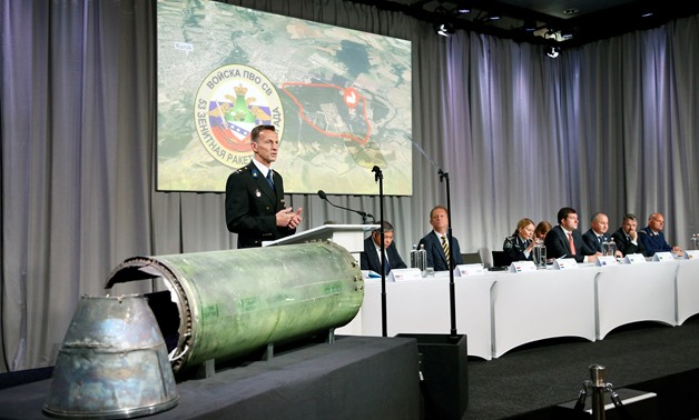 Dutch police officer Wilbert Paulissen, head of the National Crime Squad, is pictured next to a damaged missile as he presents interim results in the ongoing investigation of the 2014 MH17 crash that killed 298 people over eastern Ukraine, during a news c