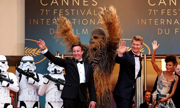 """71st Cannes Film Festival - Screening of the film """"Solo: A Star Wars Story"""" out of competition - Red Carpet Arrivals - Cannes, France May 15, 2018. Producer Simon Emanuel and cast members Joonas Suotamo, Thandie Newton and Chewbacca pose. REUTERS/Stephane"""