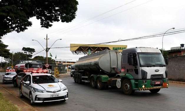 A fuel truck leaves a distrubution plant escorted by police in Brasilia