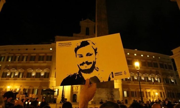 A man holds a placard during a vigil to commemorate Giulio Regeni, who was found murdered in Cairo a year ago, in downtown Rome, Italy January 25, 2017.