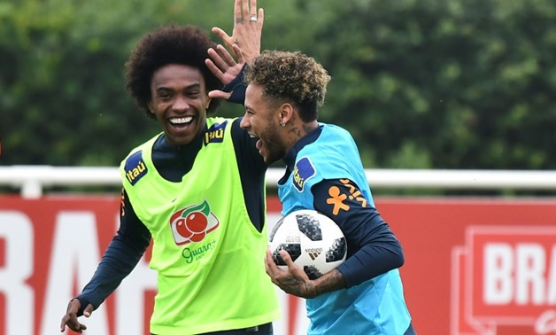 Brazil's striker Neymar (R) high-fives Willian (L) as they take part in a training session at Tottenham Hotspur's Enfield Training Centre, north-east of London ahead of their friendly with Croatia.