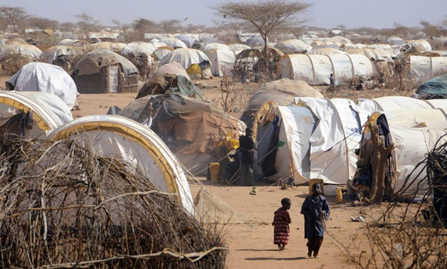 "People move around near makeshift homes, or ""tukuls"", in the outskirts of Dagahaley settlement at Kenya's Dadaab Refugee Camp. JONATHAN ERNST/REUTERS"