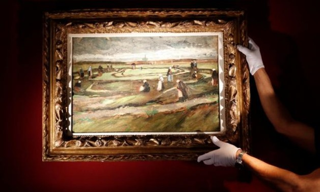 An Artcurial employee poses as he holds the painting «Raccommodeuses de filets dans les dunes, 1882» (Women Mending Nets in the Dunes) by Vincent Van Gogh during a preview for media at their auction house in Paris, France March 28, 2018. Picture taken Mar