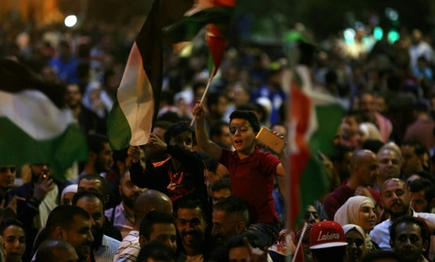 Children wave flags during a protest near the prime minister's office in Amman, Jordan, on June 4, 2018