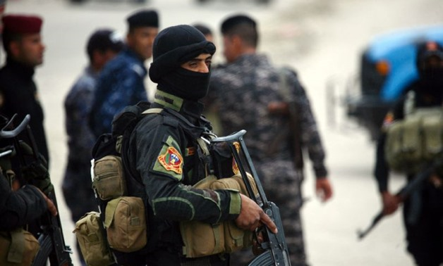 A member of Iraqi security forces stands guard at the site of a suicide attack south - AFP