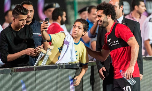 Egypt's national team footballer and Liverpool's forward Mohamed Salah greets fans during the final training session at Cairo international stadium in Cairo on June 9, 2018- AFP