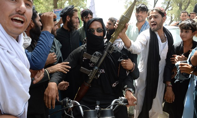 An Afghan Taliban militants carries a rocket-propelled as he looks on with residents as they took to the street to celebrate ceasefire on the second day of Eid in the outskirts of Jalalabad on June 16, 2018- AFP